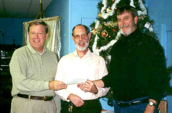 Picture of 3 men holding a check being donated to the Parsons State Hospital Endowment Association.